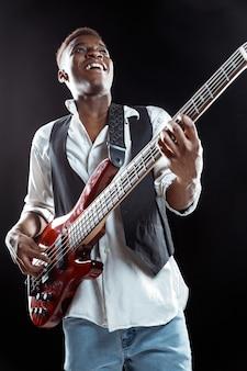Muzyk jazzowy gra na gitarze basowej w studio na czarnej ścianie