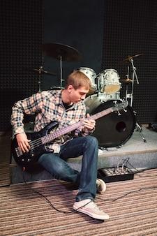 Muzyk mężczyzna gra na gitarze basowej
