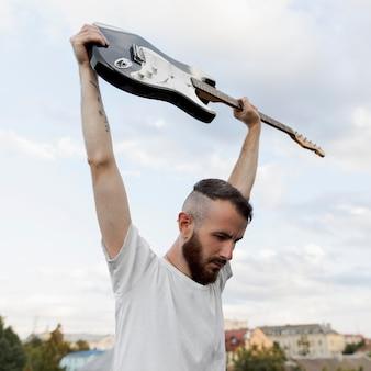 Muzyk mężczyzna trzyma gitarę elektryczną na zewnątrz
