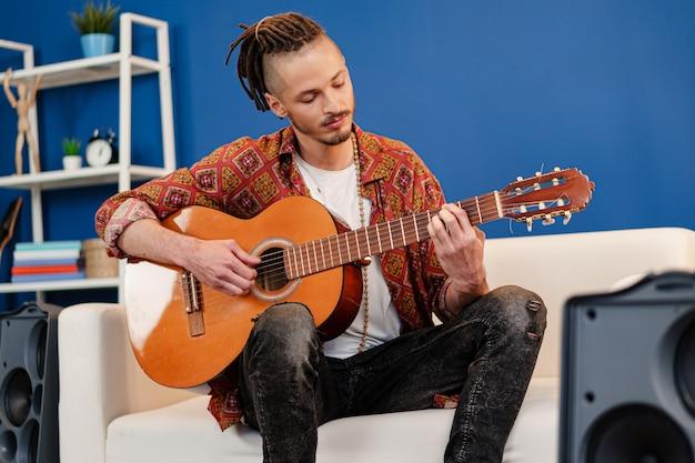 Muzyk młody facet stylowy gra na gitarze w swoim mieszkaniu