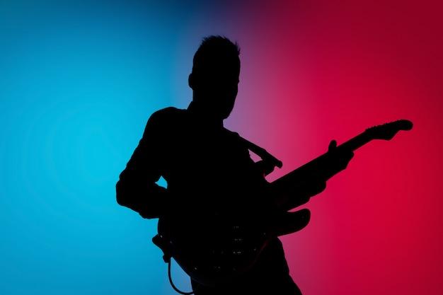 Muzyk na białym tle w ciemnym studio w świetle neonu