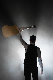Muzyk na scenie trzyma gitarę klasyczną