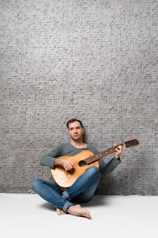 Muzyk opiera się na ścianie i gra na gitarze