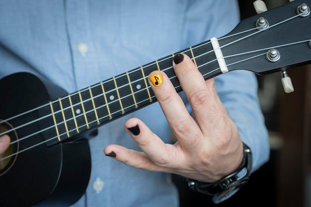 Muzyk rockowy gra na gitarze hawajskiej. ćwiczenia i zabawy w samotności. młody muzyk w pokoju. gitara reggae. nieformalny młody chłopak trzyma w rękach instrument muzyczny