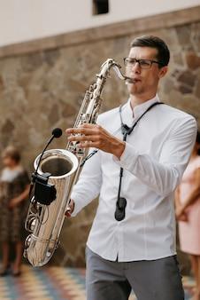 Muzyk saksofonista w białej koszuli gra na chromowanym saksofonie