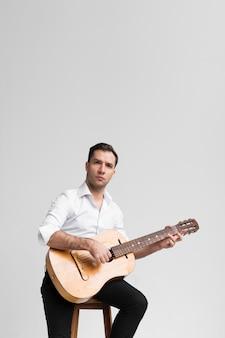 Muzyk siedzi na krześle i gra na gitarze
