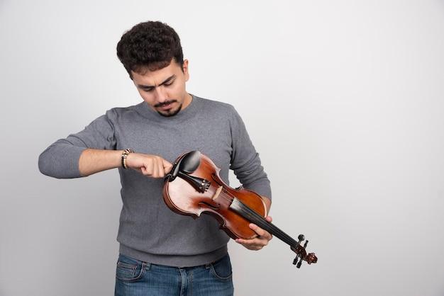 Muzyk sprawdzający i poprawiający melodię swoich skrzypiec.