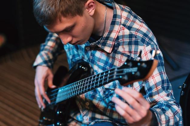 Muzyk strojący struny na gitarze basowej