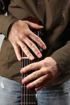 Muzyk trzyma gitarę akustyczną z bliska oburącz