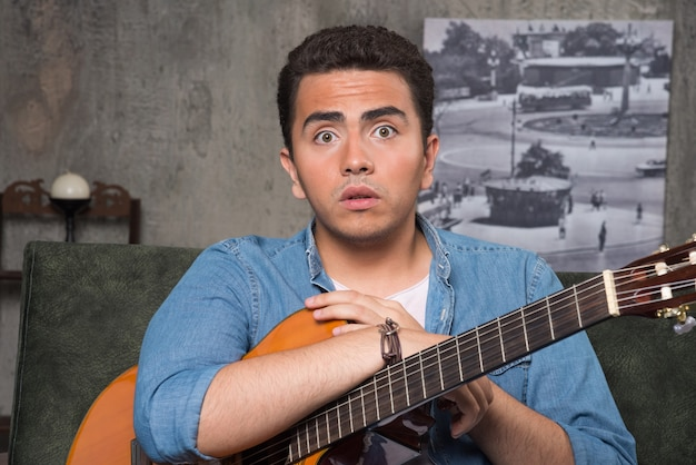 Muzyk trzyma piękną gitarę i siedzi na kanapie. wysokiej jakości zdjęcie