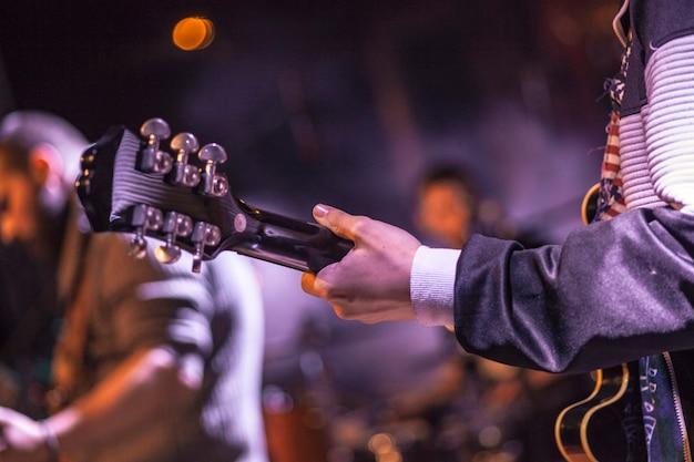 Muzyk trzymający gitarę podczas koncertu w kolorowych reflektorach