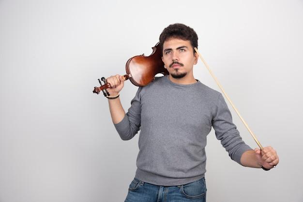 Muzyk trzymający skrzypce i myślący o kolejnym utworze do zagrania.