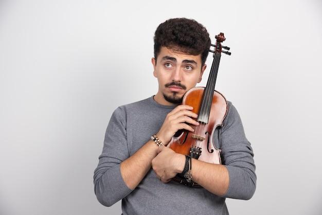 Muzyk trzymający swoje brązowe drewniane skrzypce i wygląda na zestresowanego.