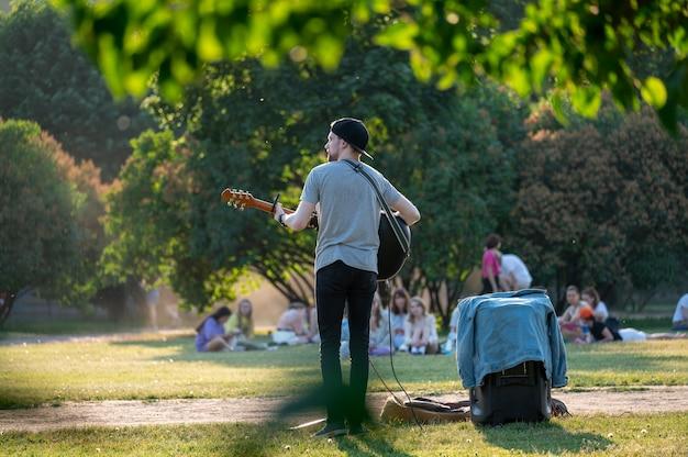 Muzyk uliczny gra na gitarze w parku. letni zielony park, muzyk rockowy daje bezpłatny koncert w parku. mężczyzna w miejskim parku z gitarą
