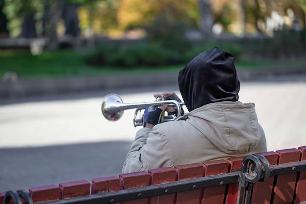 Muzyk uliczny siedzi na ławce i gra na trąbce.