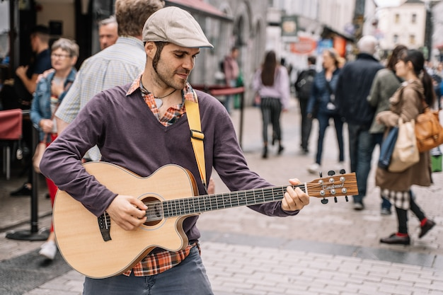 Muzyk uliczny z gitarą w mieście.