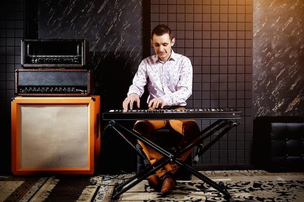 Muzyk w lekkiej koszuli gra na syntezatorze fortepianowym w ciemnym studiu nagrań