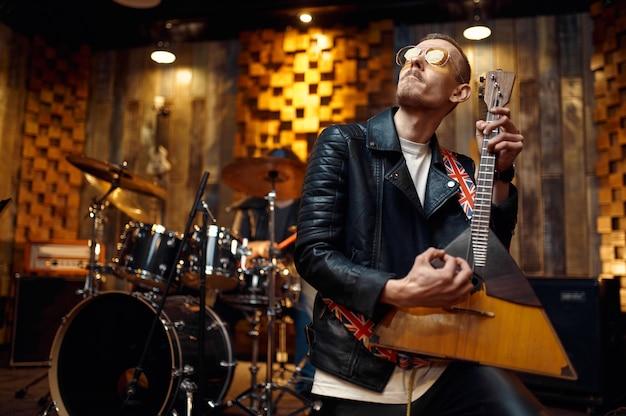 Muzyk w okularach grający na bałałajce, muzyka występująca na scenie. występ zespołu rockowego lub powtórka w garażu, mężczyzna ze smyczkowym instrumentem muzycznym, wykonawca dźwięku na żywo