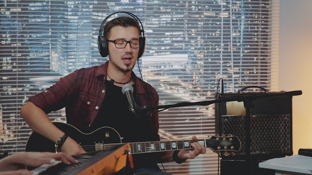 Muzyk w słuchawkach i modne ubranie nagrywa swoją nową piosenkę w domowym studio