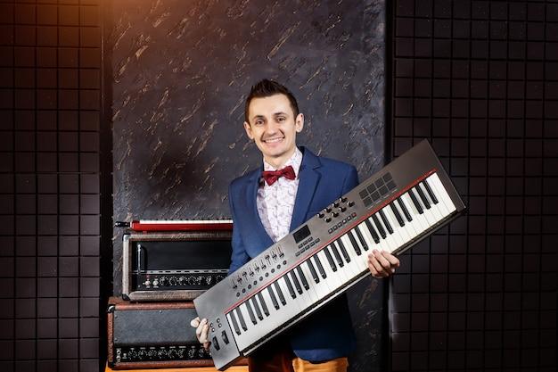 Muzyk z syntezatorem w rękach w studiu nagrań