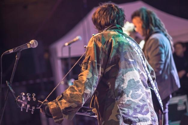 Muzyk z tyłu gra na koncercie rockowym oświetlonym niebieskimi reflektorami