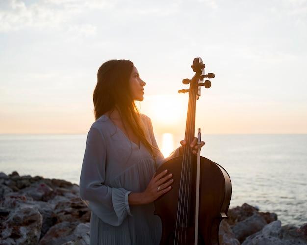 Muzyk z wiolonczelą na zewnątrz o zachodzie słońca