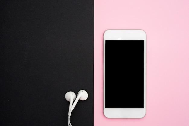 Muzyka, gadżety, miłośnik muzyki. biały smartfon i słuchawki na czarnym i miękkim różowym tle ze słuchawkami.