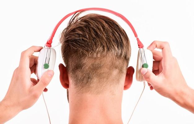 Muzyka jest tym, czym jestem. seksowny muskularny mężczyzna słuchać dźwięku. człowiek w słuchawkach na białym tle. e-książka. nieogolony mężczyzna słuchania książki audio. widok z tyłu męskiej szyi ze słuchawkami.