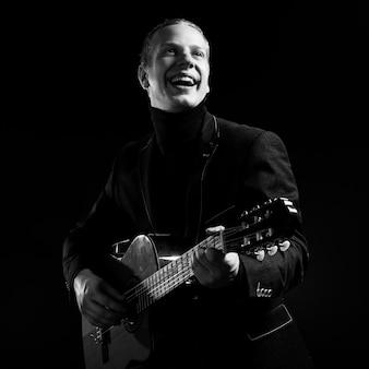 Muzyka. młody muzyk w czarnym garniturze trzyma gitarę