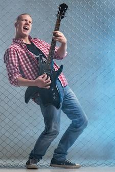 Muzyka. młody muzyk z gitarą na ścianie ogrodzenia
