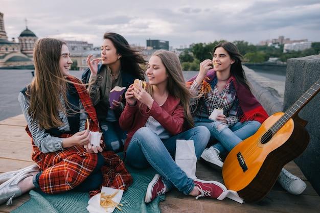 Muzyka na gitarze akustycznej i spotkania z bliskimi przyjaciółmi na dachu. uśmiechnięte dziewczyny z fast foodami, niezwykłe miejsca do odpoczynku i komunikacji, wspólne spędzanie czasu, koncepcja wesołej i radosnej atmosfery