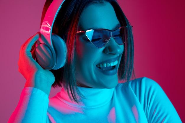 Muzyka. portret kobiety kaukaski na różowym tle studio w modnym świetle neonu. piękna modelka ze słuchawkami. pojęcie ludzkich emocji, wyraz twarzy, sprzedaż, reklama, moda.