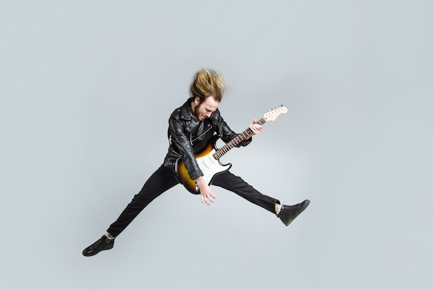 Muzyka rockowa. brodaty mężczyzna skacze z gitarą. gitara elektryczna. przystojny mężczyzna z gitarą. brutalny mężczyzna z gitarą elektryczną.