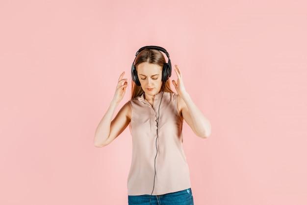 Muzyka, rozrywka, hobby. młoda piękna dziewczyna słucha muzyki w dużych czarnych słuchawkach,. pragnienie sztuki, radość z kreatywności.