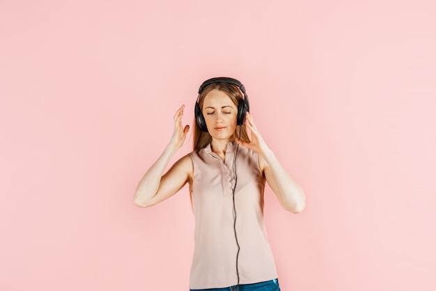 Muzyka, rozrywka, hobby. młoda piękna dziewczyna słucha muzyki w dużych czarnych słuchawkach, różowa ściana. pragnienie sztuki, radość z kreatywności.