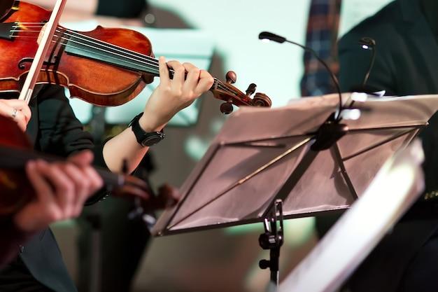 Muzyka symfoniczna. kobieta gra na skrzypcach w orkiestrze w pobliżu stojaka na nuty.