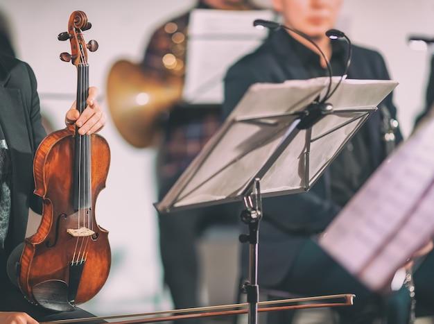 Muzyka symfoniczna. kobieta trzyma skrzypce w orkiestrze w pobliżu stojaka na nuty. stonowany w stylu vintage.