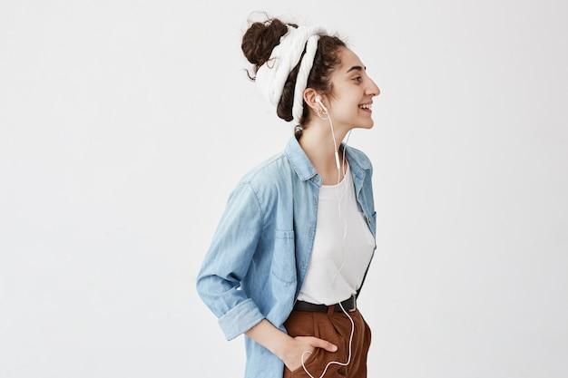 Muzyka, szczęście i technologia. urocza stylowa dziewczyna z hairbun, trzyma dłoń w kieszeni brązowych spodni, słucha muzyki na telefonie komórkowym, pozuje na białej ścianie z miejscem na reklamę