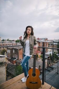 Muzyka ulicy. młoda dziewczyna z gitarą akustyczną na dachu miasta. wolność, wypoczynek, styl życia młodzieży, koncepcja młodego barda i kompozytora