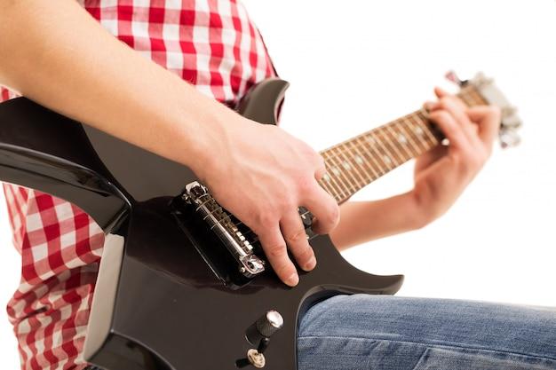 Muzyka, zbliżenie. młody muzyk trzyma gitarę elektryczną