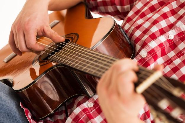 Muzyka, zbliżenie. muzyk trzyma drewnianą gitarę