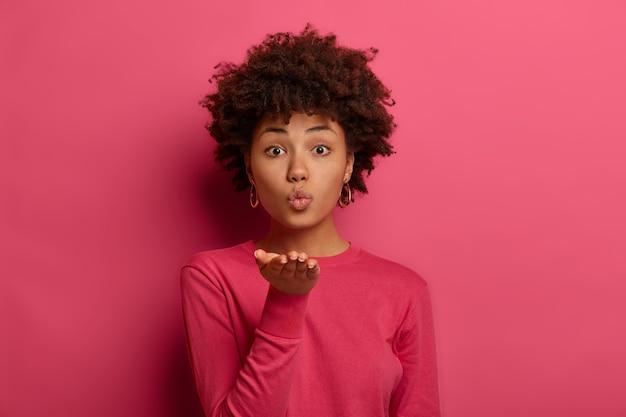Mwah dla ciebie. śliczna kręcona kobieta przesyła buziaka, ma złożone usta, flirtuje z mężem, wyraża romantyczne uczucia
