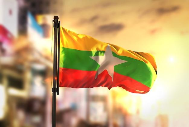 Myanmar flaga przeciwko miastu rozmyte tło w sunrise podświetlenie