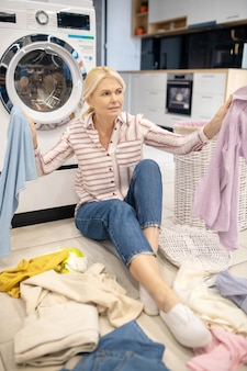 Mycie. blondynka gospodyni w pasiastej koszuli siedzi w pobliżu pralki z dużą ilością ubrań