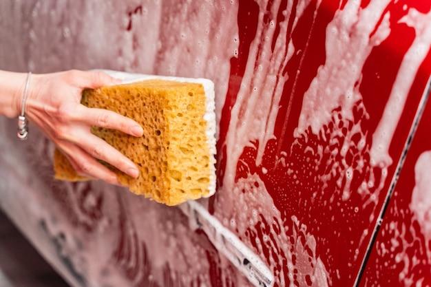 Mycie czerwonego samochodu spienioną żółtą gąbką. ręka kobiety mycie samochodu na myjni samochodowej.