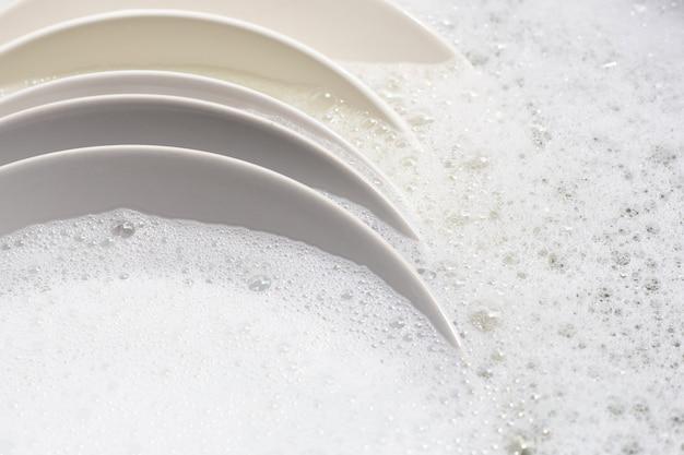 Mycie naczyń, brudne naczynia moczone w zlewie kuchennym.