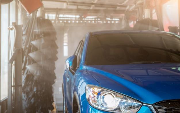 Mycie niebieskiego suv-a za pomocą automatycznej myjni samochodowej