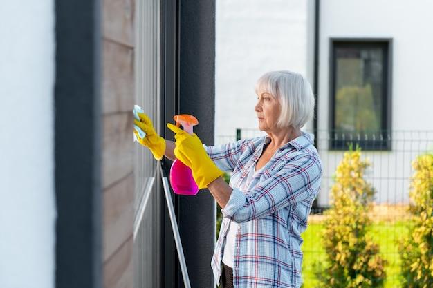 Mycie okien. dojrzała piękna kobieta ubrana w żółte rękawiczki podczas mycia okien letniego domu