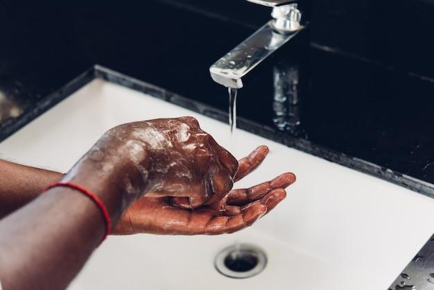 Mycie rąk czarnego mężczyzny ocierającego się mydłem i wodą w zlewach, aby zapobiec epidemii koronawirusa