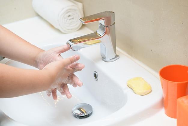 Mycie rąk dziecko mydło do płukania bieżącą wodą w zlewie,